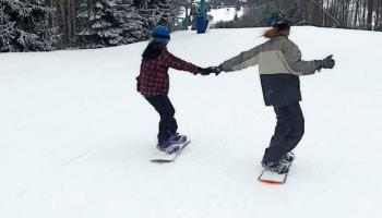snow boarders holding hands going down trail