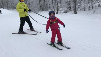 girl learning how to ski with dad